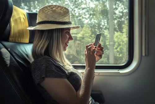 woman_sitting_at_train_and_looking_to_mobil_phone_under_sunlight_at_day_time