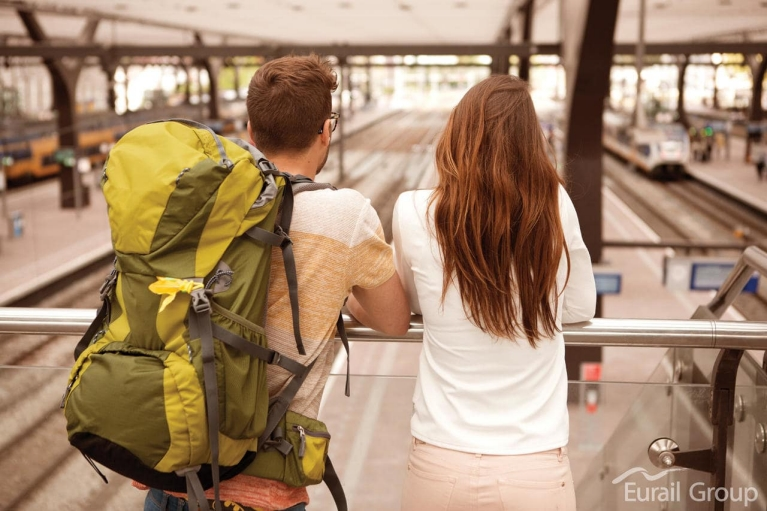 Man with a green backpack and girl in a white jumper lean against a rail while looking into a train station