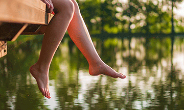 woman-sitting-on-jetty-dangling-feet-over-water